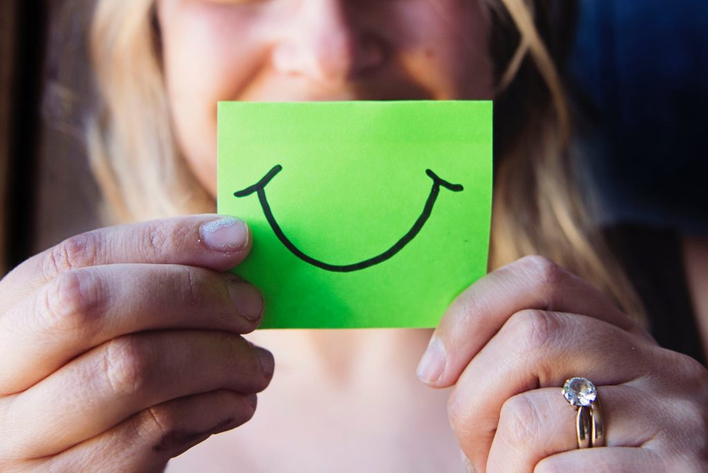 Woman holding a sticky note with a smile on it
